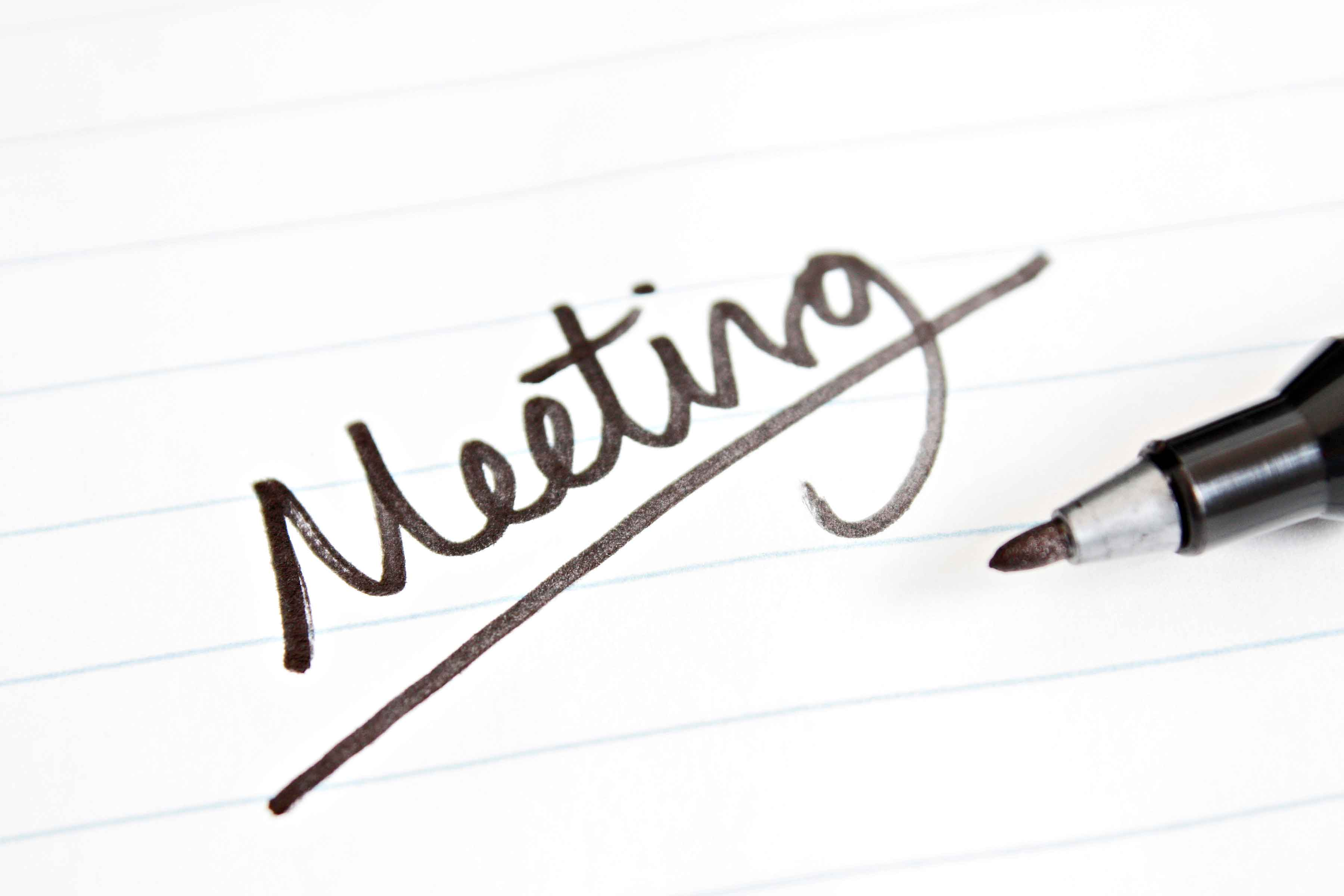 The word meeting scrawled on a piece of paper with a black pen beside it.