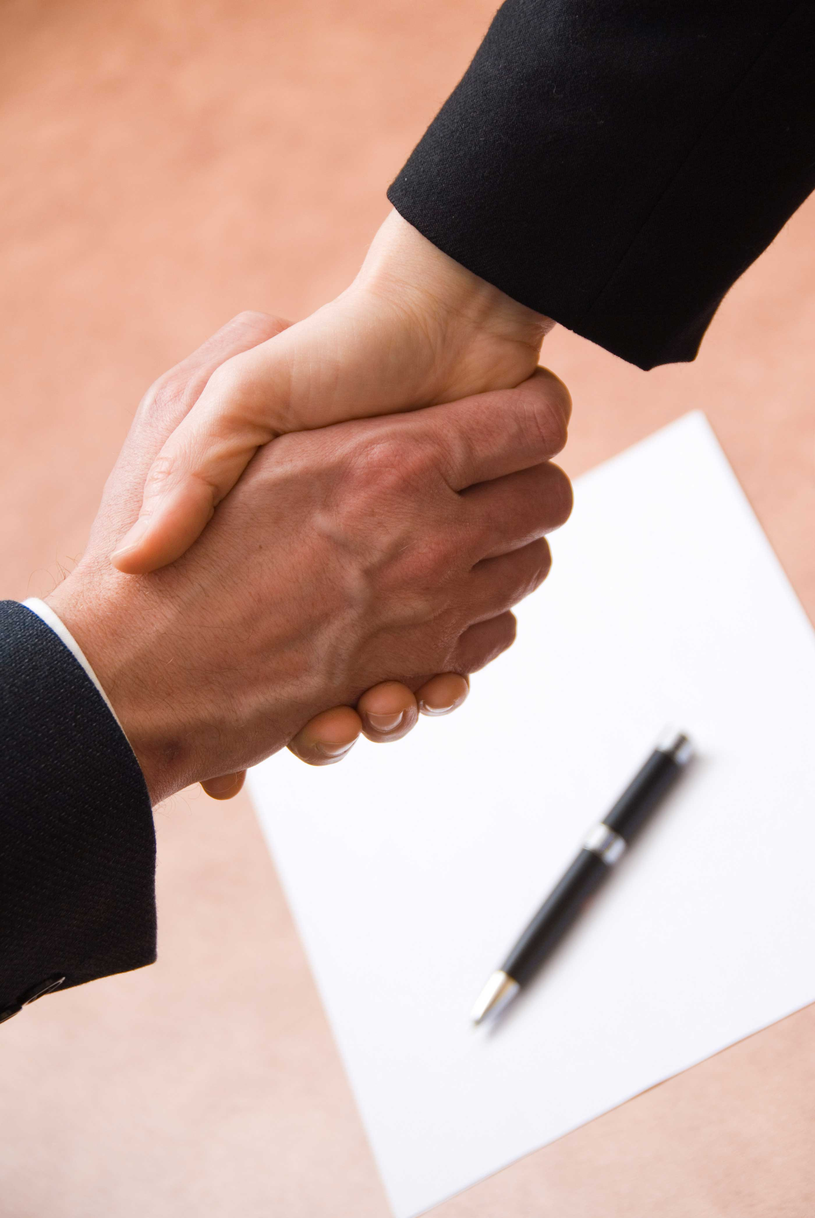 A man and a woman shake hands over a contract.