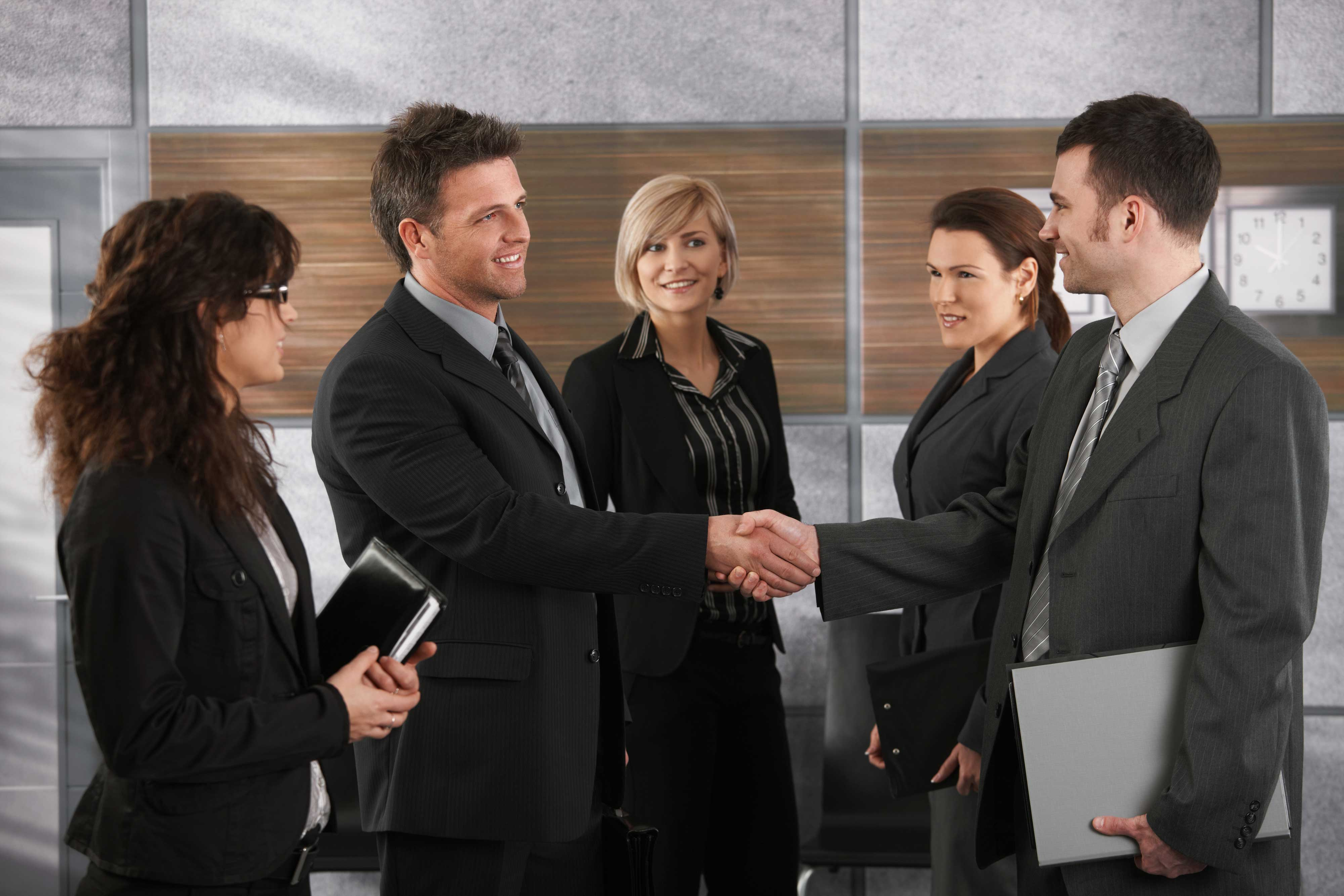Five business people networking. Two are shaking hands.